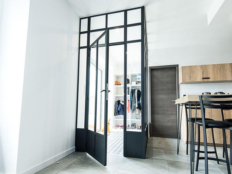verrière avec porte battante entre l'entrée et la pièce à vivre